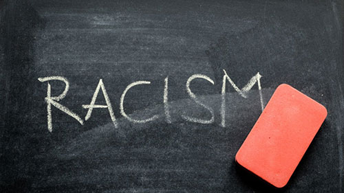 Chalkboard with the word Racism in all capital letters with an eraser on top of the chalkboard