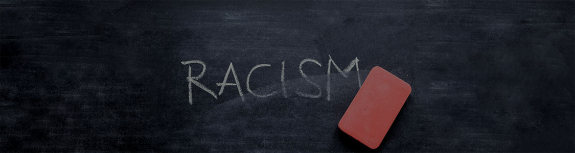 Chalkboard with an eraser and the word Racism in all capital letters